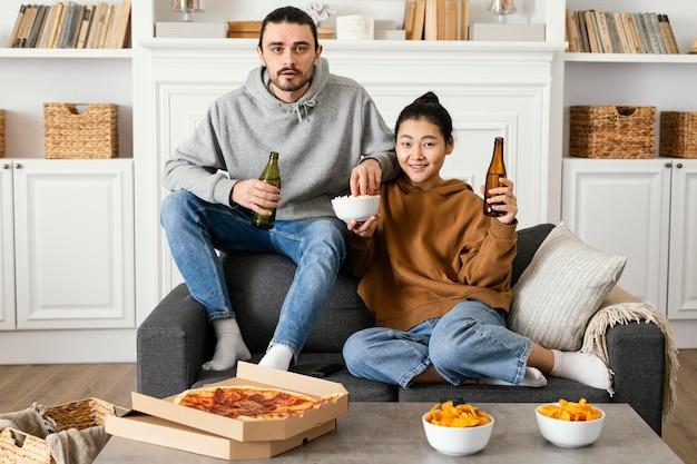 Paar trinkt bier und isst snacks drinnen