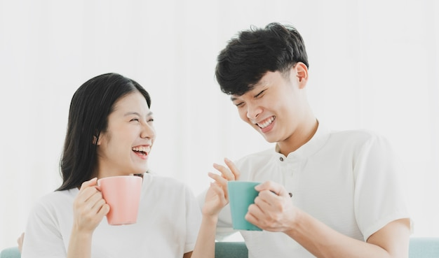 Paar trinkt kaffee auf dem sofa mit glücklichem ausdruck