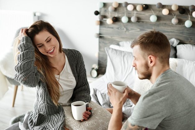 Paar trinkt morgenkaffee im schlafzimmer