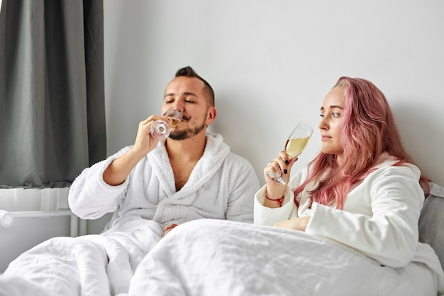 Paar trinkt sekt, kaukasischer mann und frau haben ruhe, die weißen hausmantel zu hause trägt