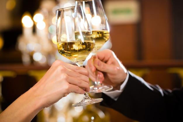 Paar trinkt wein und stößt mit den gläsern an, nahaufnahme