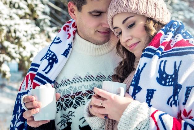 Paar umarmt und hält tasse kaffees mit eibisch