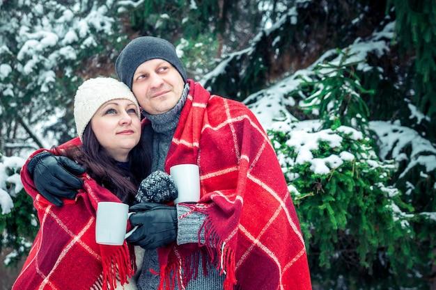 Paar umarmt und hält tassen kaffee