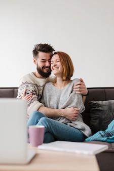 Paar umarmt und verwischt dekor mit laptop