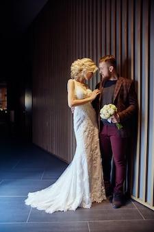 Paar umarmte und küsste sich nach der hochzeit. braut und bräutigam umarmen sich und schauen ihnen in die augen. liebe, zärtlichkeit, treue und fürsorge bei jeder berührung