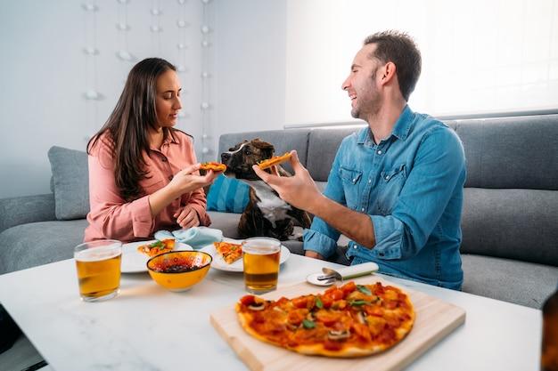 Paar und ihr hund sitzen auf dem sofa und essen hausgemachte italienische pizza in ihrem wohnzimmer