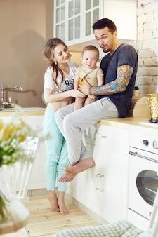 Paar und ihr kleines baby baby in den armen. junge familie zu hause morgens an einem freien tag, der in der küche sitzt. freudige und fröhliche gesichter, die sich umarmen und spaß haben