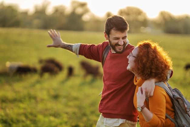 Paar verbringen freizeit in der natur an einem schönen sonnigen herbsttag. paar umarmt und geht.