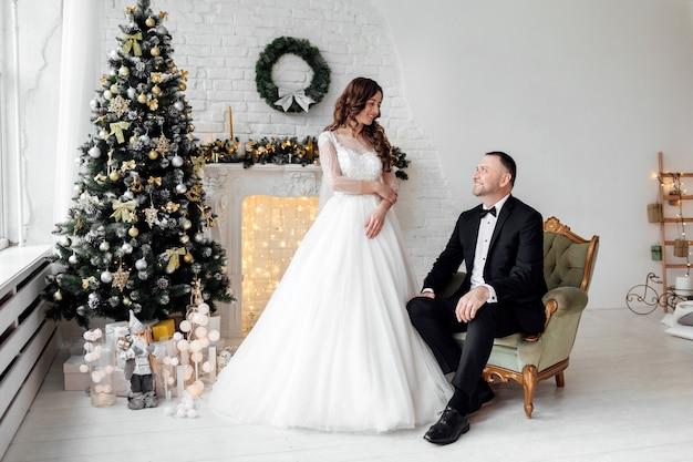 Paar verliebt braut und bräutigam posiert im studio. geschmückt mit weihnachtsbaum