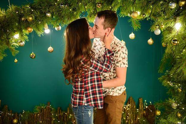 Paar verliebt in der nähe von weihnachtsdekorationen junges paar küsst in der nähe von weihnachtsbaum. zurückhaltend. silhouette.