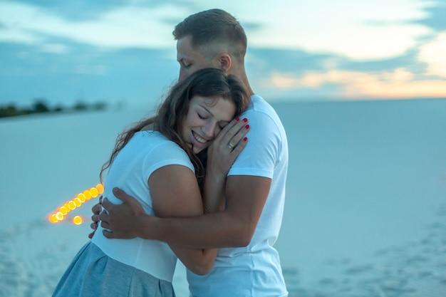 Paar verliebt romantische umarmungen in sandwüste. abend, romantische atmosphäre, in sand brennen kerzen.