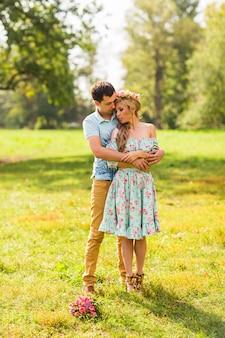 Paar verliebt schöne junge männer, die in einem sommerpark an einem sonnigen tag umarmen.