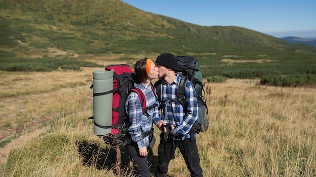 Paar verliebte touristen mann und frau stehen auf einer bergebene und küssen sich leidenschaftlich