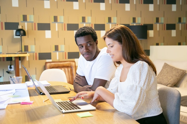 Paar verschiedene designer, die mit laptops und blaupausen am tisch sitzen und designprojekt diskutieren