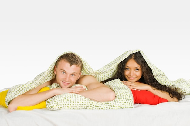 Paar versteckt unter hüllen im bett