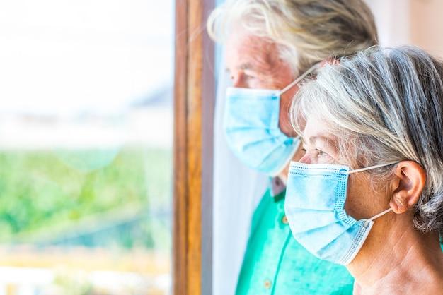 Paar von zwei älteren und reifen menschen, die von zu hause aus nach draußen schauen und eine maske tragen, um coronavirus zu verhindern - lockdown-lebensstil