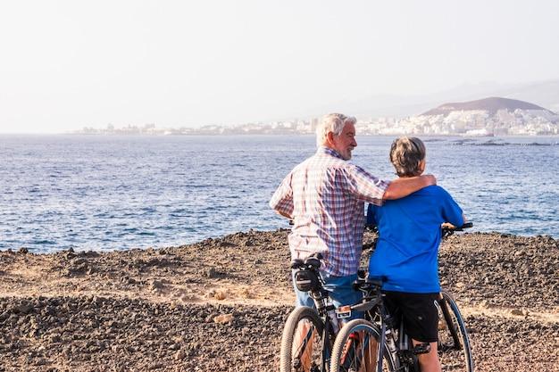 Paar von zwei älteren und reifen personen mit ihren fahrrädern in einer isolierten zone mit blick auf das wasser des meeres am strand - fitness-lifestyle für erwachsene