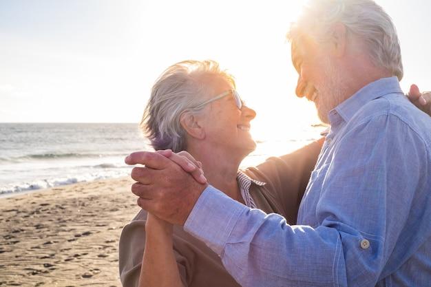 Paar von zwei alten und reifen glücklichen senioren, die den sommer gemeinsam am strand auf dem sand tanzen, mit dem sonnenuntergang im hintergrund. rentner- und freizeitlebensstil