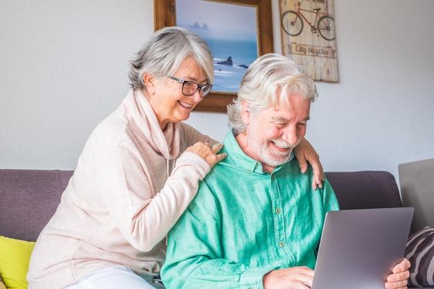 Paar von zwei alten und reifen leuten zu hause mit tablet zusammen im sofa. senioren verwenden laptop, der spaß hat und es genießt, ihn anzusehen. freizeit- und freizeitkonzept