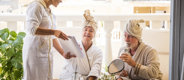 Paar von zwei gesunden und glücklichen senioren, die einen massage- und behandlungsservice mit einer assistentin nehmen und spaß haben