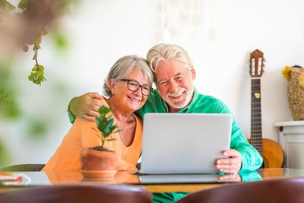 Paar von zwei glücklichen reifen und alten leuten oder senioren zu hause, die auf dem sofa sitzen und spaß haben, gemeinsam einen laptop oder computer zu suchen und zu benutzen