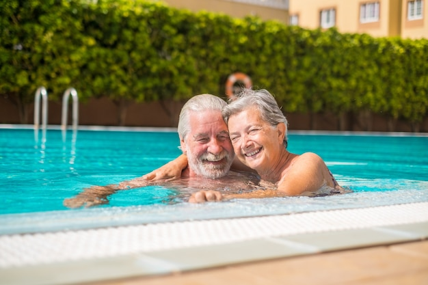 Paar von zwei glücklichen senioren, die spaß haben und gemeinsam im schwimmbad lächeln und spielen. glückliche leute, die den sommer im freien im wasser genießen
