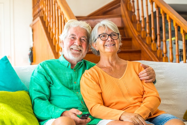 Paar von zwei glücklichen senioren, die zu hause auf dem sofa sitzen, fernsehen und um die fernbedienung des fernsehers kämpfen