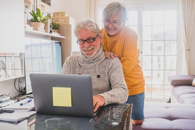 Paar von zwei glücklichen senioren, die zu hause zusammen arbeiten und laptop benutzen, lächeln und gemeinsam spaß haben - lockdown-lifestyle