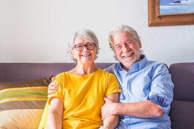 Paar von zwei glücklichen senioren oder reifen menschen, die zu hause auf dem sofa lächeln und in die kamera schauen - porträt von rentnern, die drinnen auf der couch sitzen
