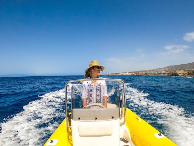 Paar von zwei glücklichen senioren und reifen leuten, die ein kleines boot oder beiboot benutzen und fahren