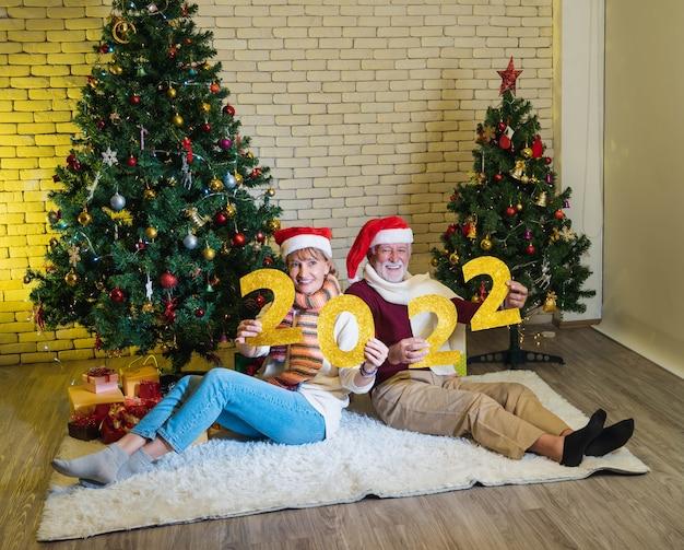 Paar von zwei glücklichen und fröhlichen senioren, die gelbe glitzerzahlen des neuen jahres 2022 halten - feiern neues jahr, neues leben und weihnachten zu hause. geschmückter weihnachtsbaum im wohnzimmer.
