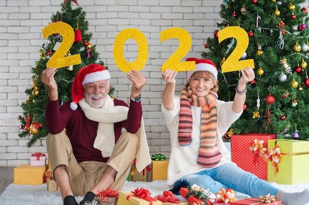 Paar von zwei glücklichen und fröhlichen senioren, die gelbe glitzerzahlen des neuen jahres 2022 zusammenhalten und neues jahr, neues leben und weihnachten zu hause feiern. geschmückter weihnachtsbaum im wohnzimmer.