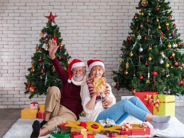 Paar von zwei glücklichen und fröhlichen senioren mit weihnachtsmütze, die neujahr, neues leben und weihnachten zu hause mit dekoriertem weihnachtsbaum im wohnzimmer mit geschenken und nummer 2022 feiern. tschüss hand.