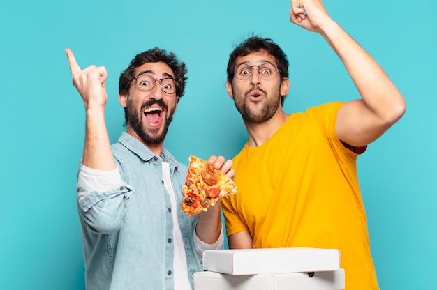 Paar von zwei hispanischen freunden, die erfolgreich einen sieg feiern und pizza zum mitnehmen halten