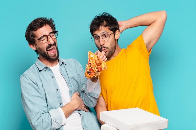 Paar von zwei hispanischen freunden glücklicher ausdruck und halten pizza zum mitnehmen?