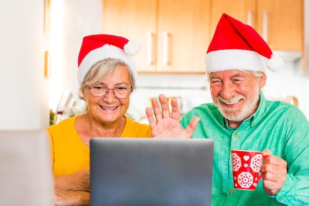 Paar von zwei senioren, die ihre familie zu hause anrufen und weihnachten mit einem laptop feiern