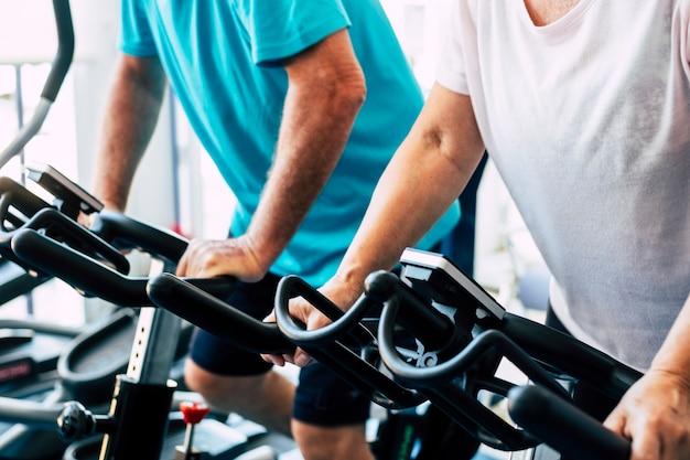 Paar von zwei senioren, die zusammen im fitnessstudio auf dem fahrrad trainieren - gesundes lebensstilkonzept - aktive rentner, die hart arbeiten