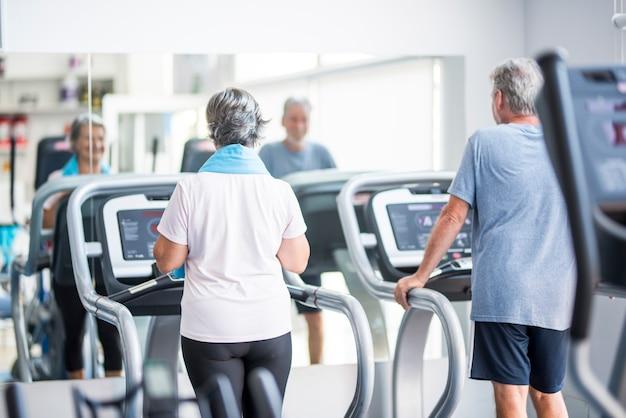 Paar von zwei senioren in beziehung zum freundschaftstraining zusammen auf dem laufband oder tapirulan - laufen im fitnessstudio und aktiver lebensstil