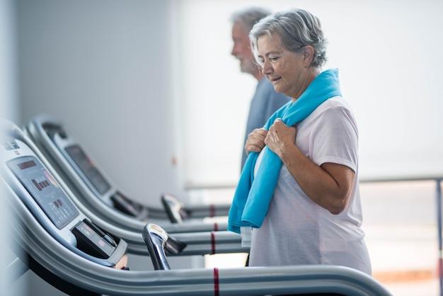 Paar von zwei senioren und reifen leuten, die zusammen im fitnessstudio trainieren - gesundes und fitness-lifestyle-konzept - wandern in einem tapirulan