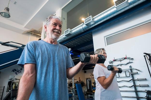 Paar von zwei senioren und reifen leuten im fitnessstudio, die sport treiben - erwachsene, die eine hantel halten und bizeps zusammen arbeiten