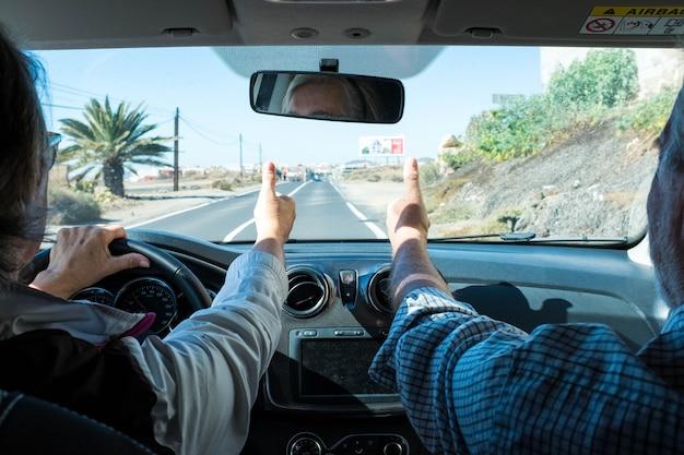 Paar von zwei senioren zusammen in einem auto, das mit ihren händen das ja-zeichen macht - aktive reife frau, die mit ihrem ehemann ein auto fährt