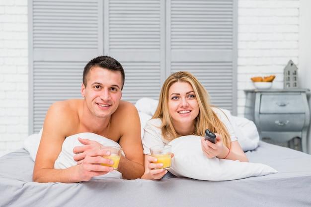 Paar vor dem fernseher im bett liegend