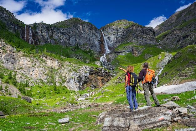 Paar wanderer, die wasserfall auf berg betrachten