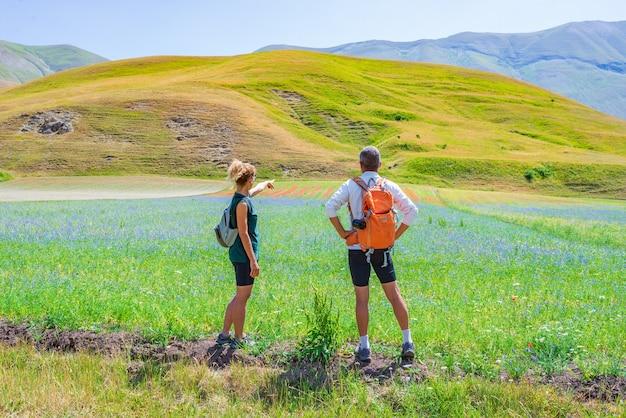 Paar wandern in blühenden feldern, berühmte farbenfrohe blühende ebene im apennin, hochland von castelluccio di norcia, italien. linsenkulturen, roter mohn und blaue kornblumen.