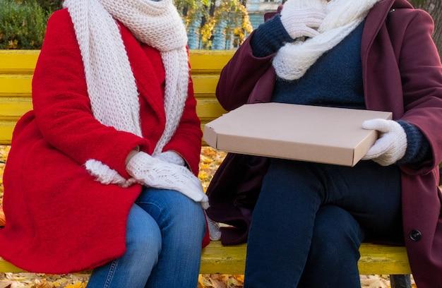 Paar weibliche hände, die paketbox mit pizza halten. konzept lieferung und zum mitnehmen