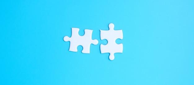 Paar weiße puzzleteile auf blauem hintergrund. lösungskonzept, mission, erfolg, ziele, zusammenarbeit, partnerschaft, strategie und puzzletag