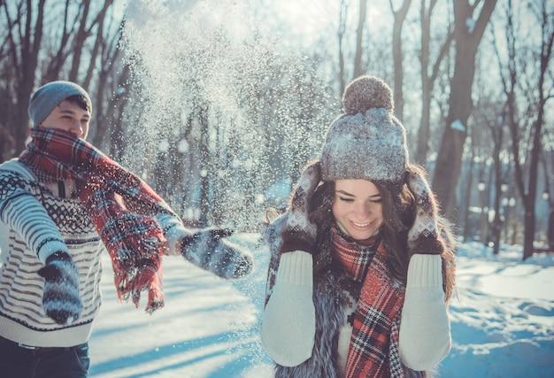 Paar wirft schnee im winterpark. leute, die spaß haben