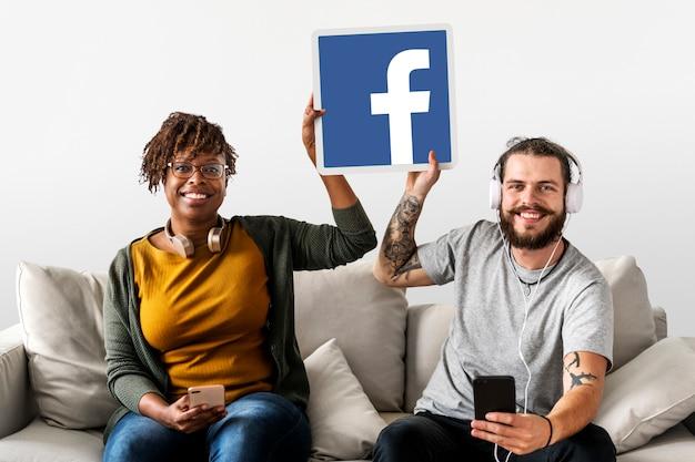 Paar zeigt ein facebook-symbol