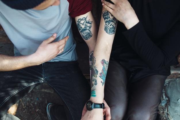Paar zeigt ihre tätowierungen auf den armen