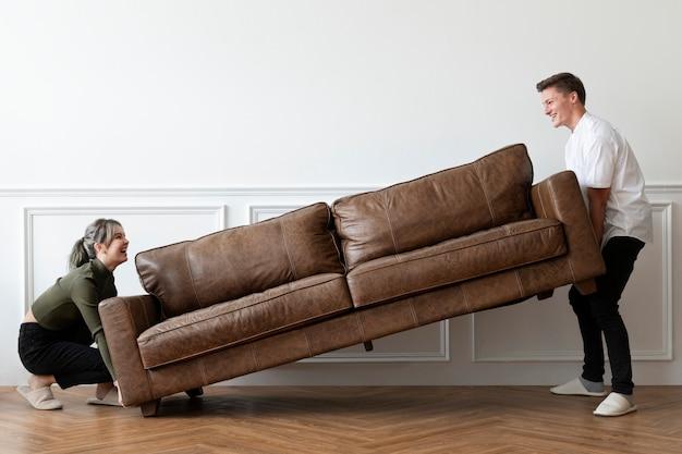 Paar zieht ein sofa in ein neues zuhause um